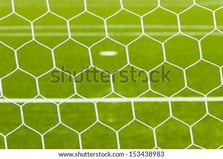 Soccer net on green grass - stock photo