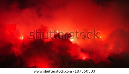 Soccer or football fans using pyrotechnics - stock photo