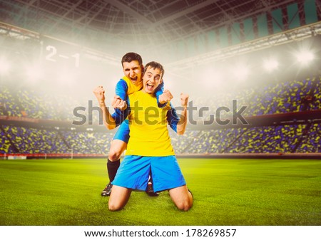 soccer or football players are celebrating goal on stadium, warm colors toned - stock photo