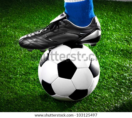 soccer payer withl with his foot on the football field - stock photo