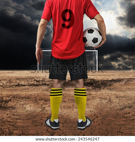 Soccer player at Neglected football field  - stock photo