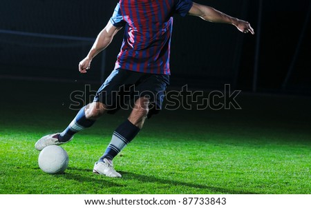 soccer player doing kick with ball on football stadium  field  isolated on black background  in night - stock photo