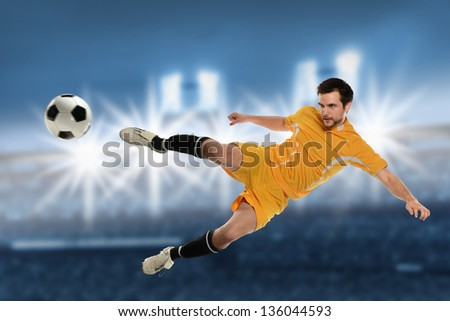 Soccer player in action kicking ball over stadium background - stock photo
