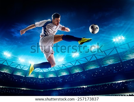 Soccer player in action on night stadium background - stock photo