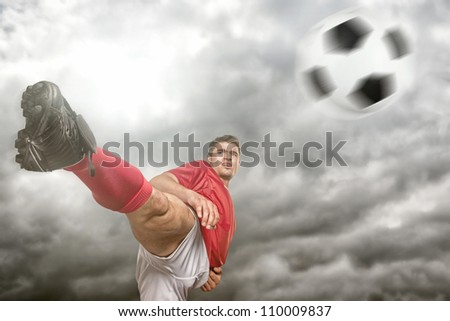 Soccer player in front of dramatic sky - stock photo