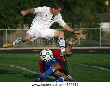Soccer player in mid-air shot on goal over fallen goalie for a score - stock photo