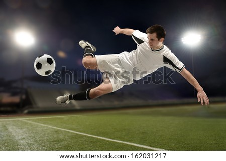 Soccer player jumping and kicking the ball inside a stadium at night - stock photo