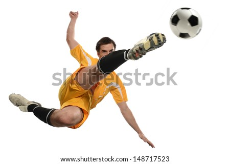 Soccer player kicking ball while jumping isolated over white background - stock photo