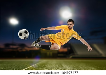 Soccer Player kicking the ball ina football stadium at night - stock photo