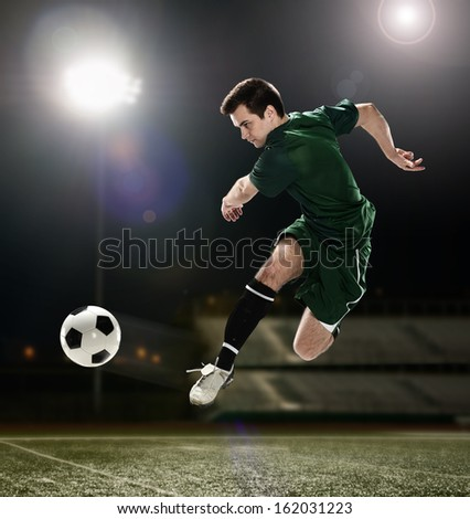 Soccer player kicking the ball with clouds on a the background - stock photo