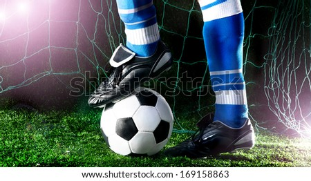 Soccer player's feet in casual pose on playing field with dark background - stock photo