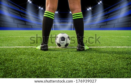 Soccer player's feet on field in stadium at night - stock photo