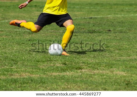 Soccer player shoot the ball with right foot on stadium - stock photo