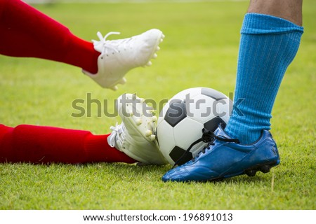 Soccer player striking the ball for defect attack team. - stock photo