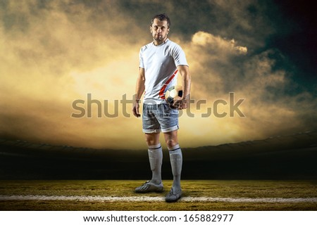 Soccer player with ball, outdoors - stock photo