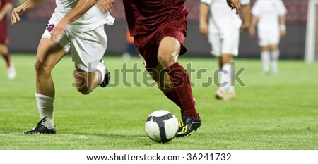 Soccer players running after the ball - stock photo