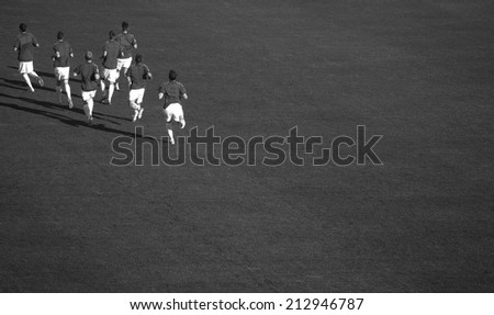 Soccer players running and warming up before a football game. black and white photography  - stock photo