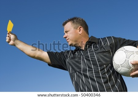 Soccer referee holding yellow card, portrait - stock photo