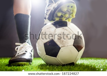 Soccer shoes & football on the green grass - stock photo