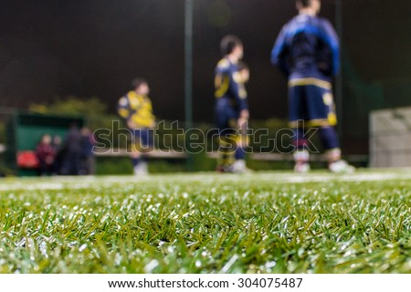 soccer team in the background listening to coach for next game. - stock photo