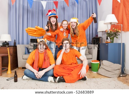 Soccer women cheering for something the guys in front fail to see. - stock photo