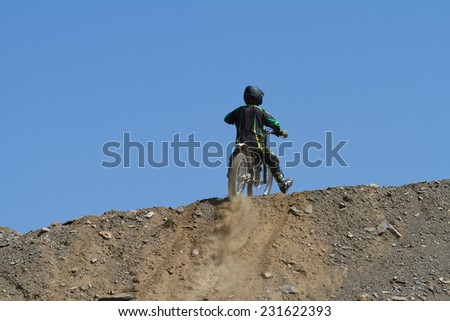 SOCHI, RUSSIA -AUGUST 16, 2014: Off-road motorcycle rider trains in summer mountains - stock photo