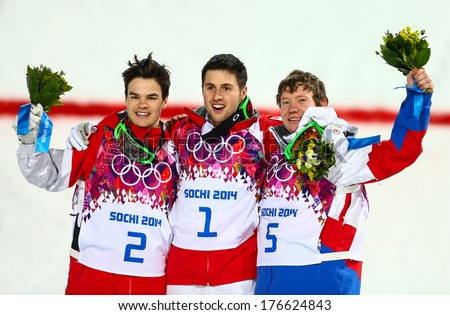 SOCHI, RUSSIA - FEB 10, 2014: KINGSBURY (CAN), BILODEAU (CAN), SMYSHLYAEV (RUS) at Men's Moguls flower ceremony of Freestyle skiing at Sochi 2014 XXII Olympic Winter Games - stock photo