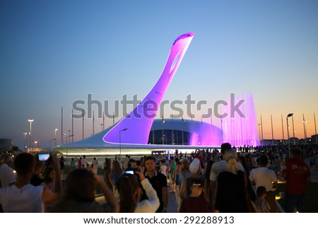 SOCHI, RUSSIA - JUL 27, 2014: Crowds of tourists walking near a bowl of the Olympic flame and singing Fountain in the Olympic park in the evening - stock photo