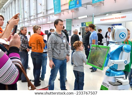 SOCHI, RUSSIA - November 21, 2014: People comminicate whith android robot in Sochi. Here there was the World Robotic Olympiad 2014. It was attended by delegates from 47 countries. - stock photo