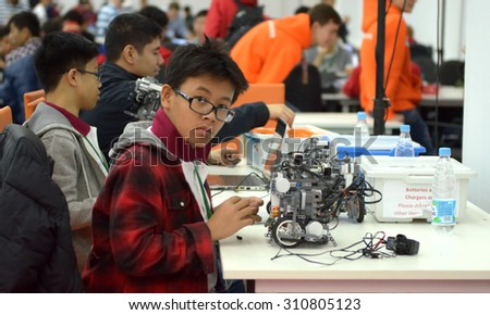 SOCHI, RUSSIA - November 21, 2014: Taiwan children make a robot at the robot Olympiad in Sochi. Here there was the World Robotic Olympiad 2014. It was attended by delegates from 47 countries. - stock photo