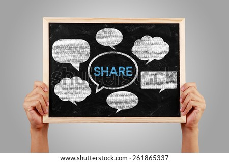 Social media concept blackboard is holden with hands against gray background. - stock photo