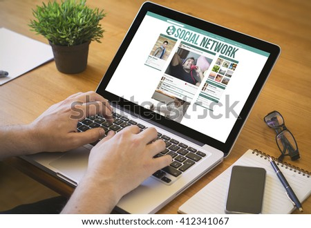 social media concept. Close-up top view of a man surfing social network  on laptop. all screen graphics are made up. - stock photo