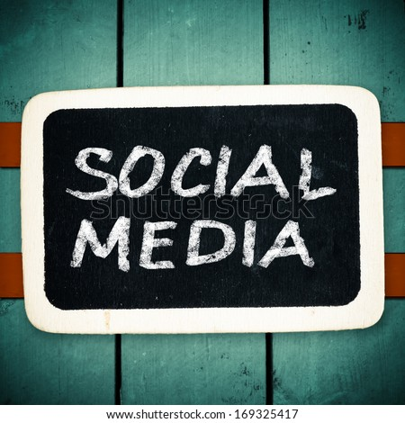 Social media concept - text on a blackboard on wood backround  - stock photo