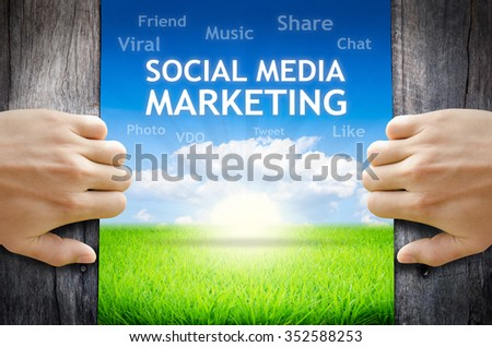 """Social Media Marketing. Hand opening an old wooden door and found wording """"Social Media Marketing"""" over green field and bright blue Sky Sunrise. - stock photo"""