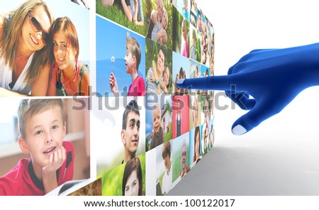 Social media network. Blue hand pointing at screen full of people, faces - stock photo