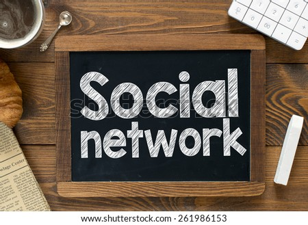 Social network handwritten on blackboard. Social network handwritten with white chalk on a blackboard, cup of coffee ,croissant, newspaper and calculator on wooden background - stock photo