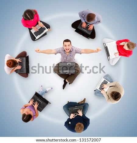 Social network members sitting with their laptop computers around a successful, happy man's circle - stock photo