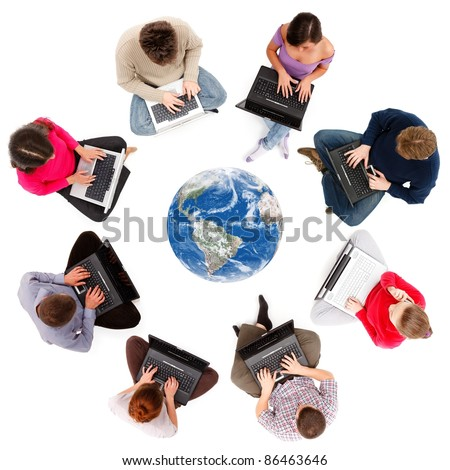 Social network members typing on laptop computers, seen from above - stock photo