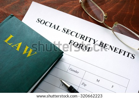 Social security benefits form on a wooden table. - stock photo
