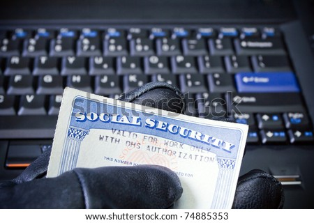 Social Security Card in computer hacker's hand, internet and  identity theft - stock photo