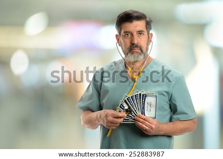 Social security concept. Senior doctor holding stethoscope to cards inside hospital building - stock photo