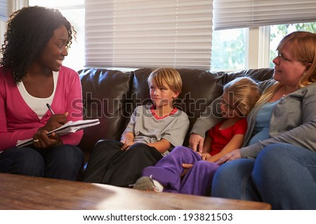 Social Worker Talking To Mother And Children At Home - stock photo