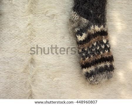 sock knitting at home against homespun woolen blankets - stock photo