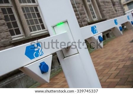Socket for electric bike battery charger with green led lights, selective focus, angled view - stock photo