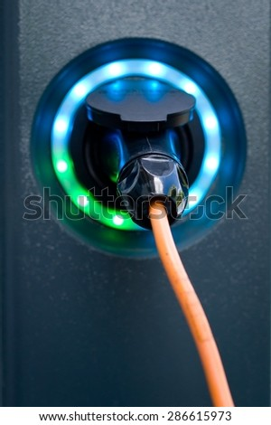 Socket for electrical car battery charger with load indicator lights, selective focus - stock photo