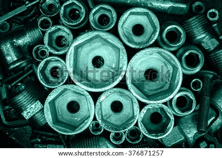 Socket spanner heads, nuts and bolts on a dark metal background. Toned. - stock photo
