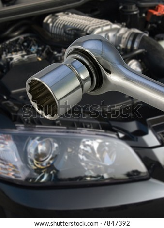 Socket spanner with V8 supercharged car engine in the background - stock photo