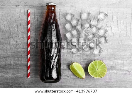 Soda bottle, ice and straw on wooden table - stock photo