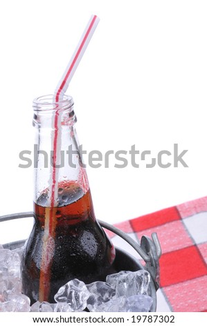 Soda bottle in bucket of ice on checkered table cloth isolated on white - stock photo