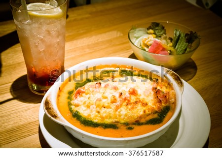 Soda drinking and Golden lasagne with meat, tomatoes, cheese sauce and pasta in alternating layers on a wooden board garnished with basil - warm and dark tone. - stock photo